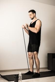 Спортивный мужчина выполняет упражнения с помощью ленты сопротивления. концепция благополучия и деятельности. сильный мужчина делает упражнения, чтобы иметь подтянутую фигуру. концепция тяжелой тренировки. человек делает упражнения для рук дома.