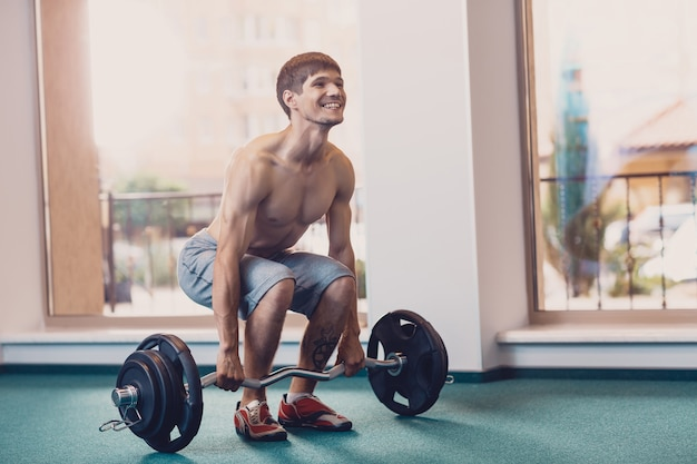 Athletic man performs workout lifting barbell