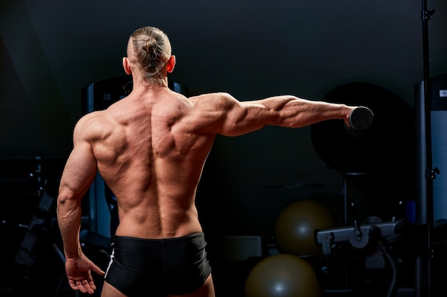 Athletic man posing. photo of man with perfect physique on black wall. back view. strength and motivation