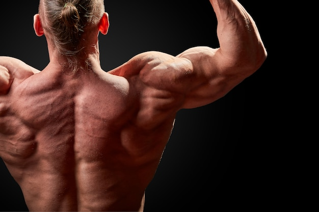 운동 남자 포즈. 검은 벽에 완벽 한 체격을 가진 남자의 사진. 다시보기. 힘과 동기