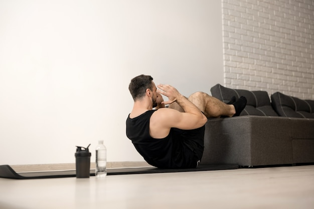 Athletic man pumping press with legs on sofa. hard workout. healthy lifestyle concept. white modern living room on background. strong man excercising to have a fit body.