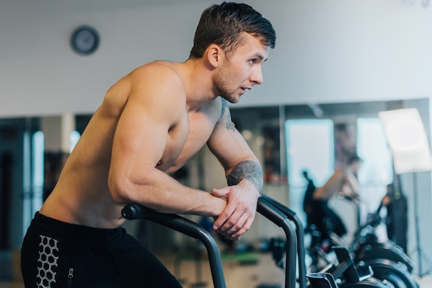Athletic man resting after workout on cycling machine