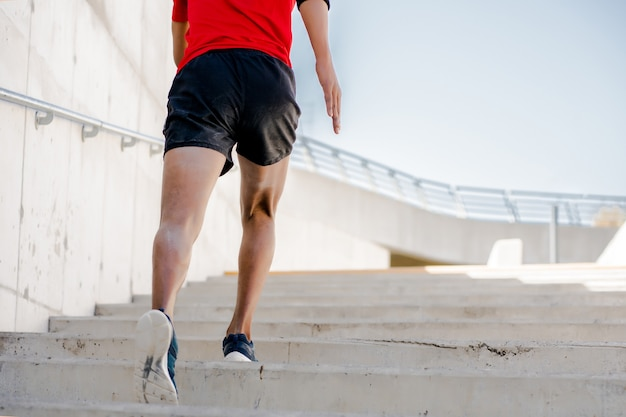 Athletic man running and doing exercise outdoors on the street
