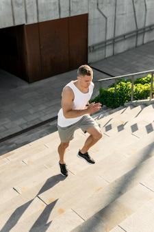 階段で走っている運動の男