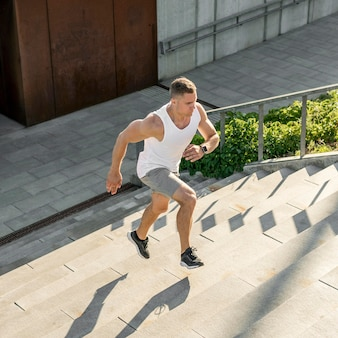 Athletic man running on stairs outdoors