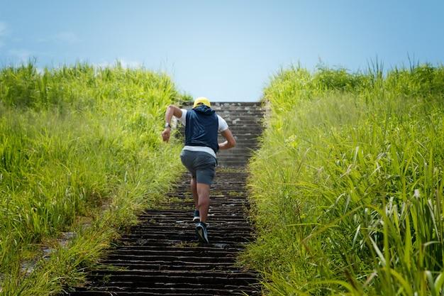 森林のトレイルで二階で走っている運動男
