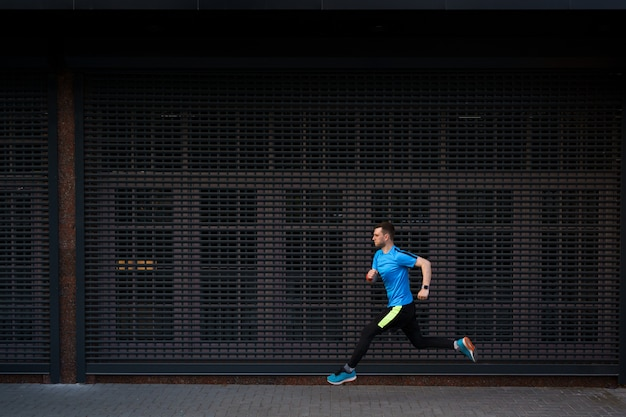 Athletic man running at urban street against grey background