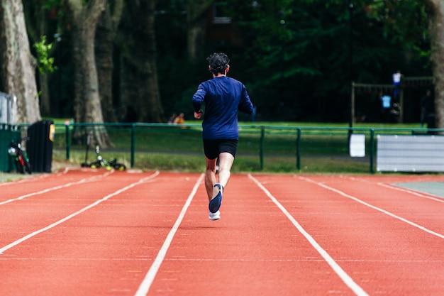 アスレチック男が走って運動を行います。ランニングトラックでのランニングの練習。