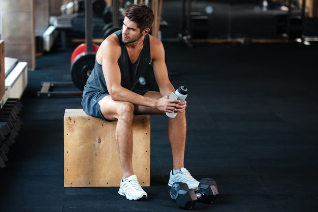 Athletic man sits on the box and looking away. in gym
