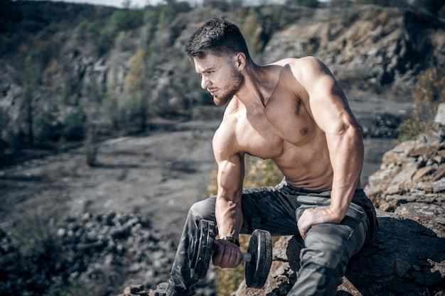 ダンベルで岩の上に座っている運動選手。採石場の背景。屋外トレーニング。