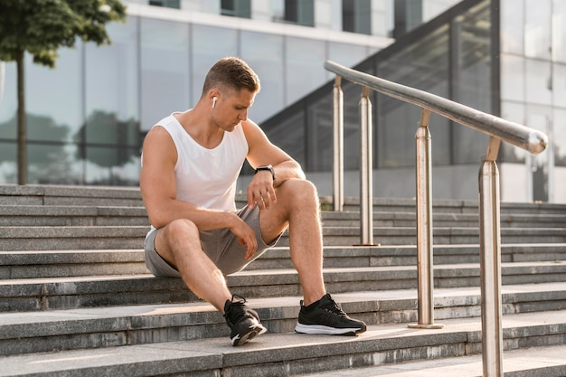 Спортивный человек сидит на лестнице на открытом воздухе