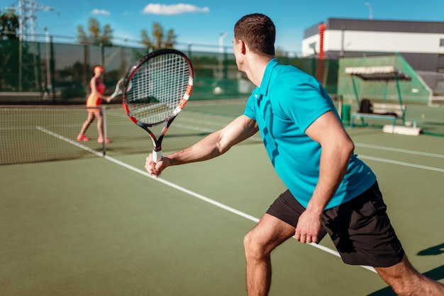 Athletic man and slim woman on tennis training on outdoor court