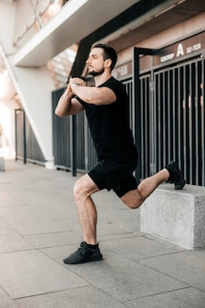 Athletic man stretching legs before workout outdoors. active living. urban sport concept. runner in black sportswear excercising at morning holding hands in lock. morning warm up.