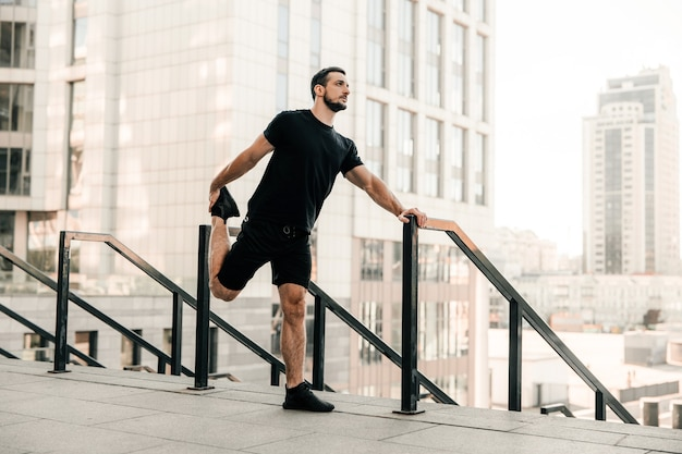 Athletic man stretching legs before workout outdoors. runner in black sportswear excercising at morning holding handrail. active living. morning city on background. morning warm up.