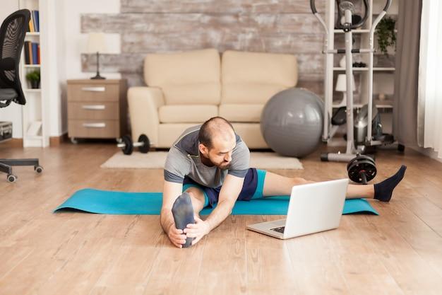 Спортивный мужчина растягивается на коврике для йоги после онлайн-тренировки во время глобальной пандемии.