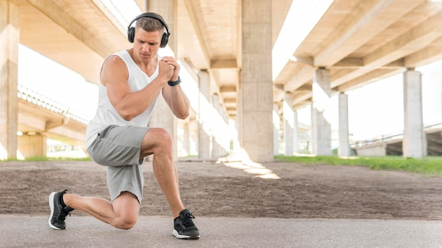 Athletic man stretching outdoors with copy space