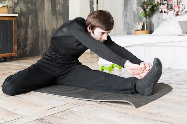 Athletic man stretching up on mat
