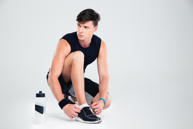 Athletic man tie shoelaces while looking away isolated