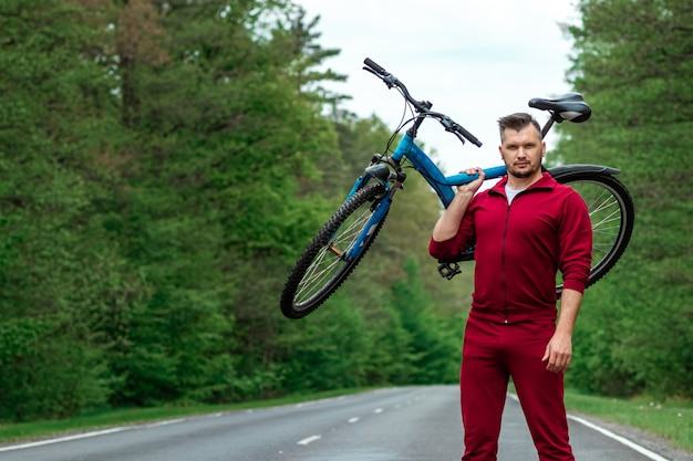 Athletic man in a tracksuit holds a bicycle on his shoulders while standing on the road in the forest. the concept of a healthy lifestyle, cardio training. copyspace.