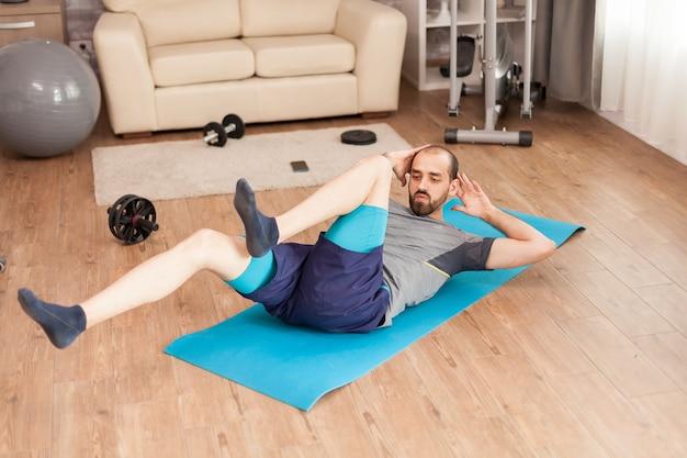 전 세계적으로 유행하는 동안 요가 매트에서 복부를 훈련하는 운동 남자.