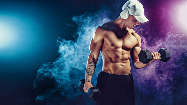 Athletic man training muscles with dumbbells in  on dark  with smoke. strong bodybuilder with six pack, perfect abs, shoulders, biceps, triceps and chest posing with headphones.