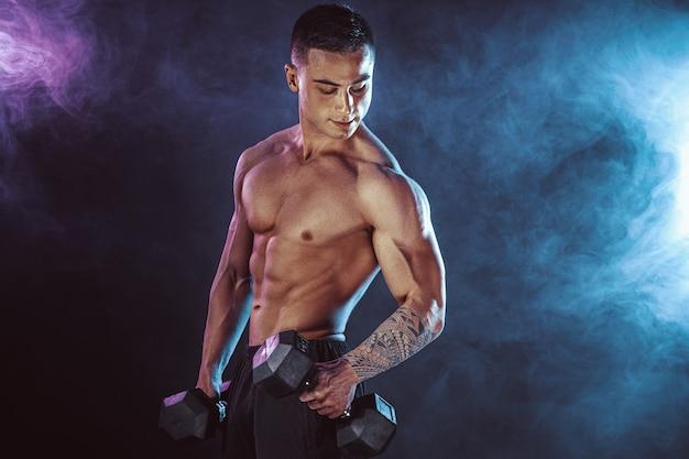 Спортивная (ый) человек тренирует мышцы с гантелями в темноте с дымом. сильный бодибилдер с шестью пакетами, идеальным прессом, плечами, бицепсами, трицепсами и грудью.