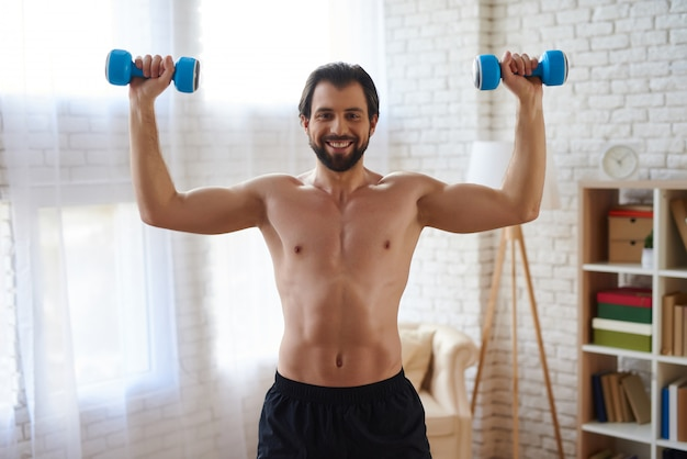 Athletic man training with pumping up muscles by dumbbells.