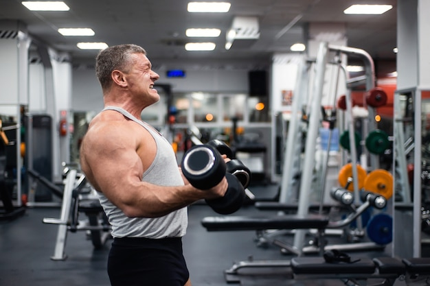 Athletic man trains in the gym.