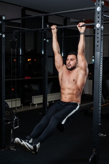Athletic man trains the muscles of the abdomen, hanging on the bar in the gym