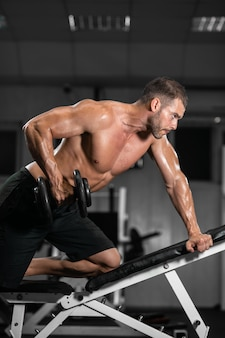 Athletic man trains with dumbbells, pumping his biceps