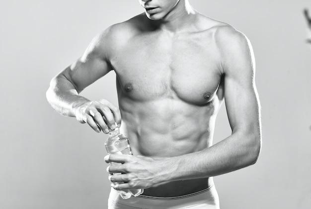 Athletic man water bottle muscular body studio posing
