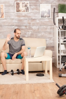 Athletic man waving at his personal trainer during online workout in time of global pandemic.