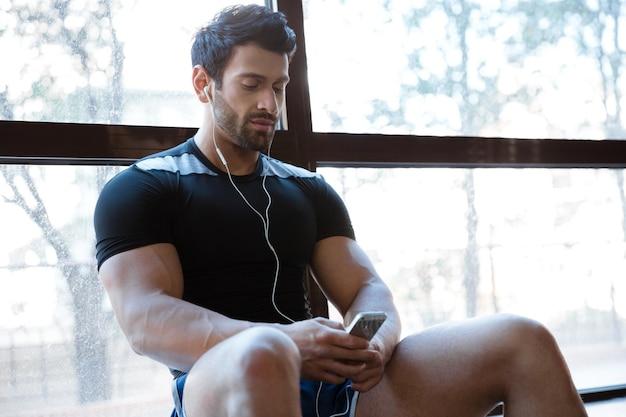 Athletic man wearing black t-shirt listening to music sitting on windowcill