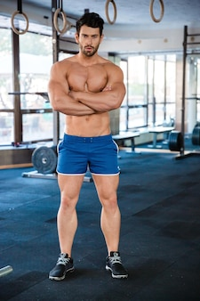 Athletic man wearing blue shorts standing with arms crossed
