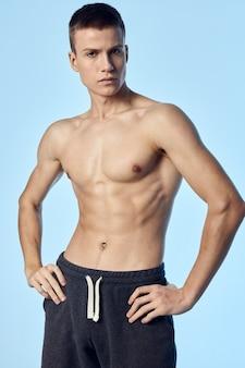 裸の胴体を持つ運動選手は、ベルトのボディービルダーの青い背景に手をつないでください