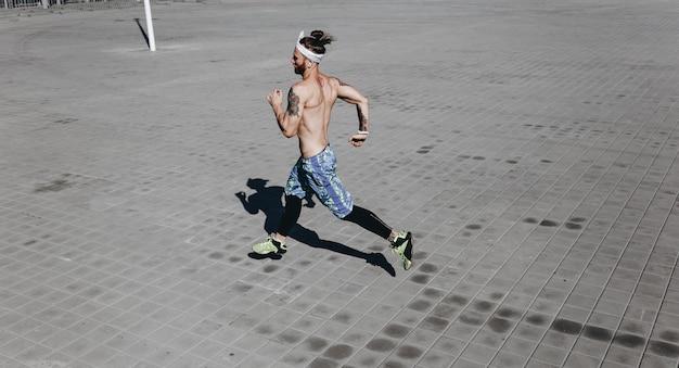 검은색 레깅스와 파란색 반바지를 입은 머리에 문신과 머리띠를 한 벌거벗은 몸통을 가진 운동 남자는 따뜻하고 화창한 날 포장용 석판을 달리고 있습니다.