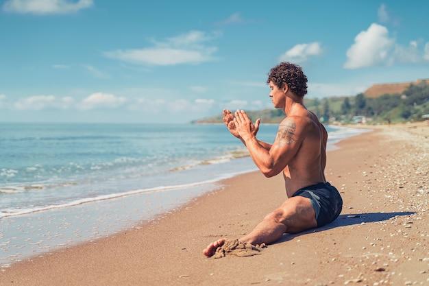 아름다운 근육을 가진 운동 남자는 해변에서 여름 훈련에 꼬기에 앉아