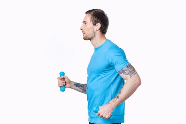 ダンベルを持つ運動選手は、白い背景の側面図をジョギングするスポーツに参加します