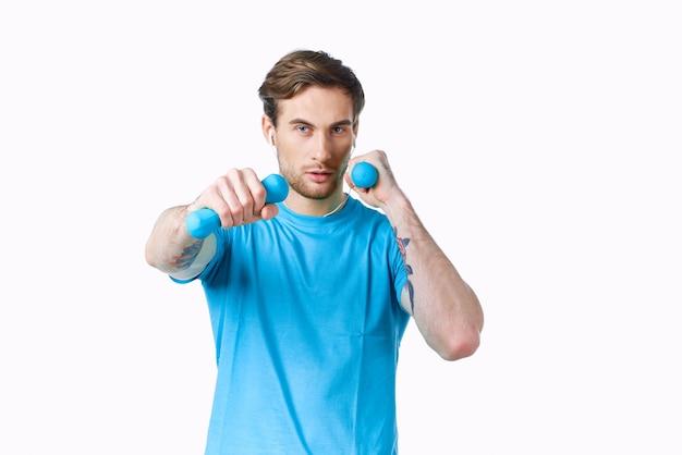 Спортивный мужчина с гантелями в руках синяя футболка обрезанный вид фитнес