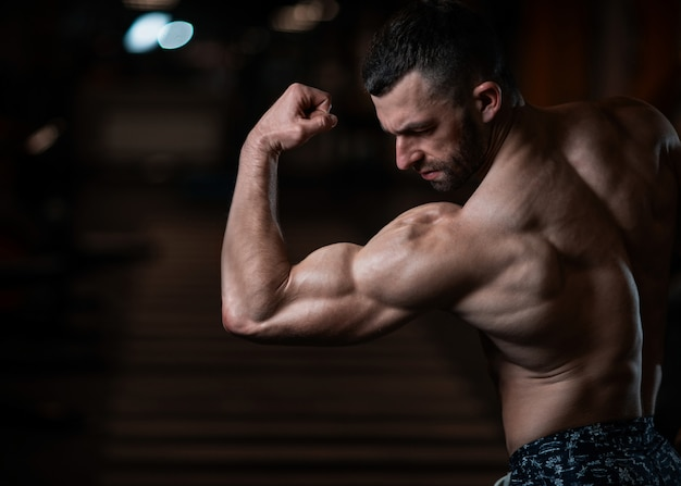 Athletic man with a muscular body poses in the gym, showing off his biceps