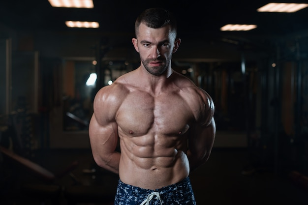 Athletic man with a muscular body poses in the gym, showing off his musclese