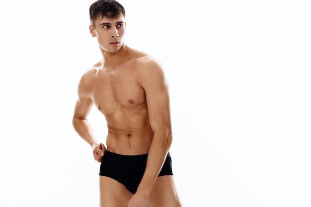 Спортивный мужчина с обнаженным мускулистым телом в темных трусиках тренировки