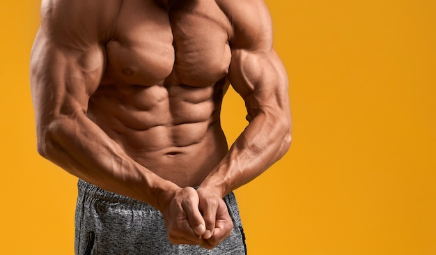 Athletic man with naked torso showing biceps