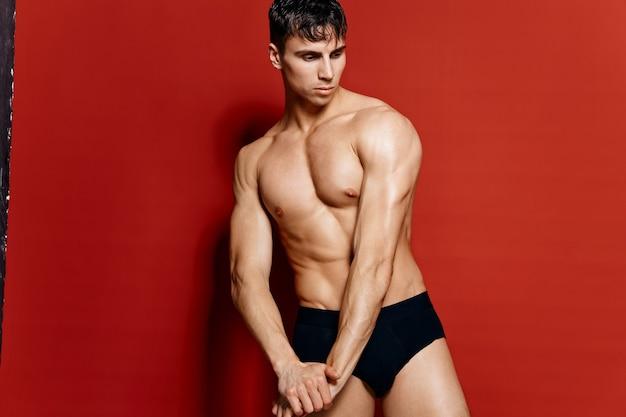 ポンプの筋肉を持つ運動選手ボディービルダーフィットネス上腕二頭筋黒パンティー赤の背景