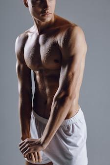 ポーズをとるポンプの筋肉を持つ運動男