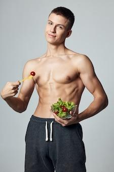 Спортивный (ый) человек с накачанным салатом здоровой пищи пресса в тренировке на тарелке