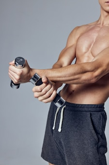 Athletic man with pumped up arms with dumbbells muscle training