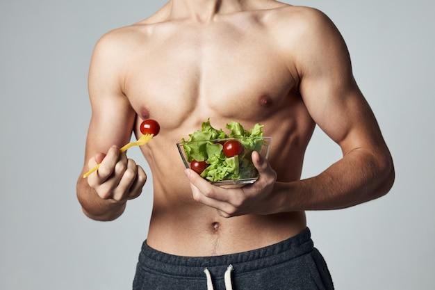 サラダの胴体プレートをポンプでくみ上げた運動選手のトリミングされた食事の眺め