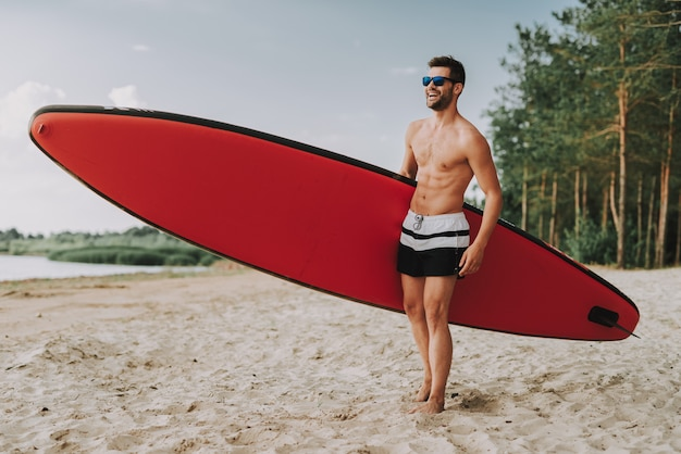 Athletic man with surf standing on beach in glasess