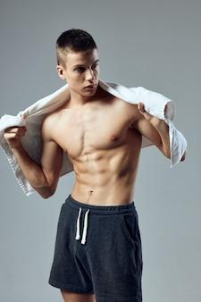 手にタオルを持った運動選手がプレスジムをポンプでくみ上げた